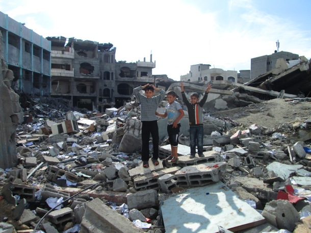 Gazan children pose on the ruins of the bombed Ministry of the Interior office (an entirely civilian building) in Gaza city three days after the end of Israel's bombing campaign.—Photo by Andy Beale