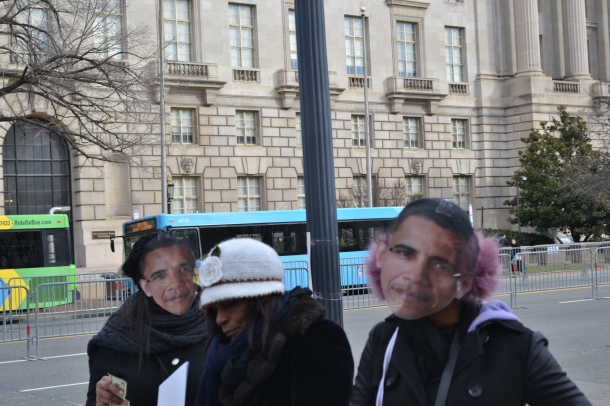 Photo By Elise Kaplan— Two girls stop to try on Obama masks sold along the designated walking route.