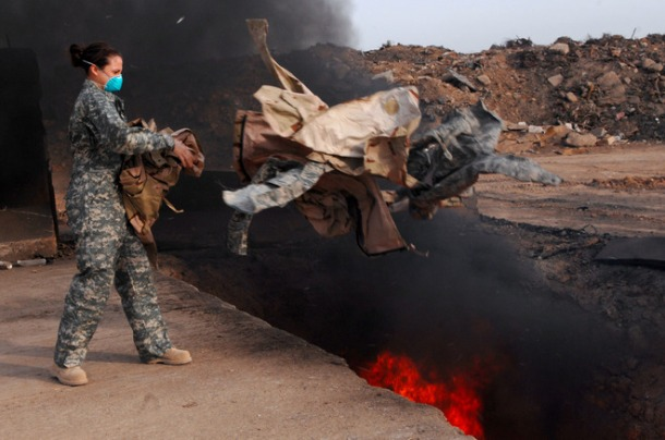 BALAD AIR BASE, Iraq — Senior Airman Frances Gavalis tosses unserviceable uniform items into a burn pit. Gavalis is deployed from Kirtland Air Force Base. (U.S. Air Force photo by Airman Julianne Showalter)