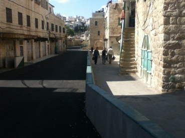 A wall down the middle of a street near Hebron's Old City divided the path used by Palestinians from the path used by Israelis. — Photo by Philipp Lausberg