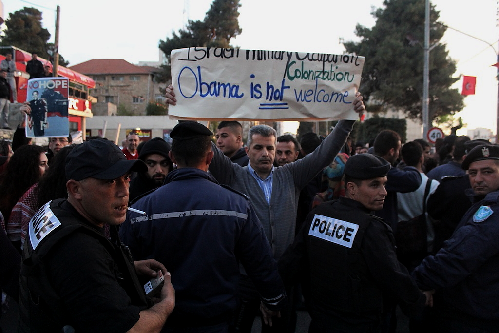 Photo by Andrew Beale—Demonstrator Hazem Kawasmi holds an anti-Obama sign in front of riot police blocking access to al-Muqata'a at a demonstration in Ramallah.