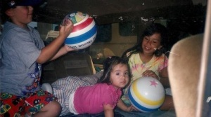 The author, Alejandra Alarcon, as a baby with her older sister Gabriela and brother Robert, in the family van. Their mother usually made the van comfortable for the long trips to Mexicali.