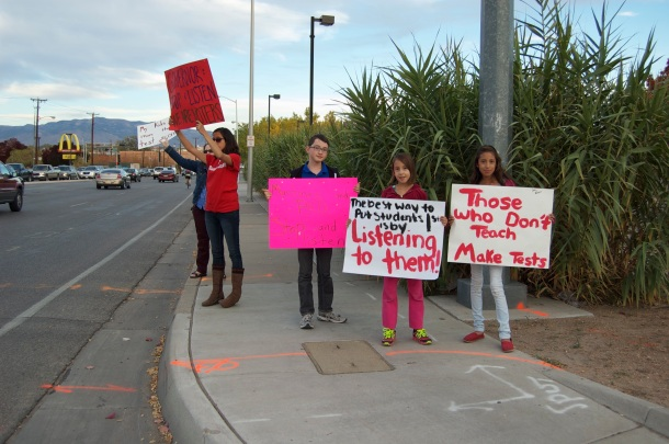 APS students Xavier Peregrino and Alma and Maya Moreno joined their parents protesting PED policies—Photo by Margaret Wright