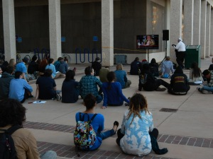 People watch the meeting on a television set up on Civic Plaza. —Credit: Robin Brown